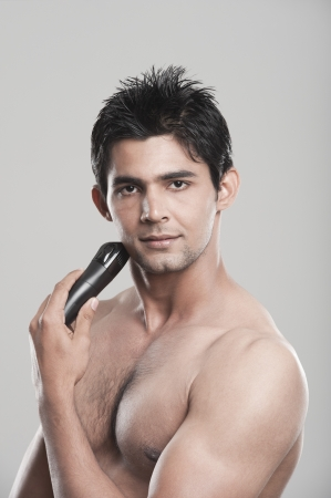 Portrait of a man shaving with electric razor photo