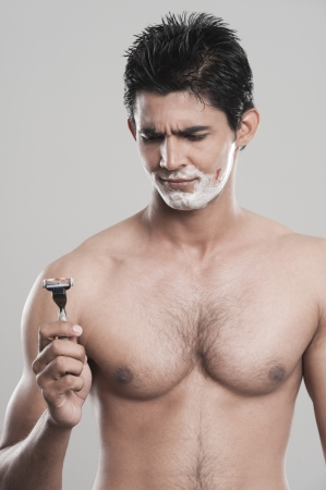 Man looking at razor with a shaving cut on face photo