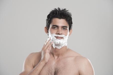 Man applying shaving cream on face photo