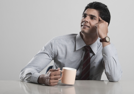 Businessman lost in thoughts while drinking coffee