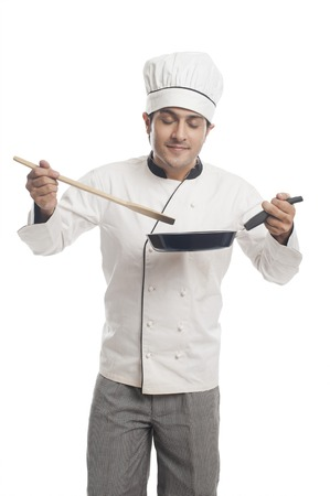Male chef preparing food in a frying pan and  smelling photo