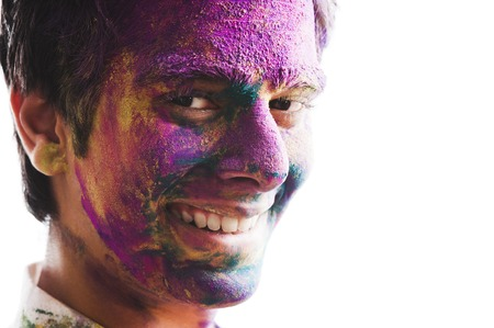 Mans face covered with powder paint during Holi festival