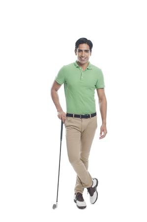 Mannelijke golfer die zich met een golfclub en glimlachend