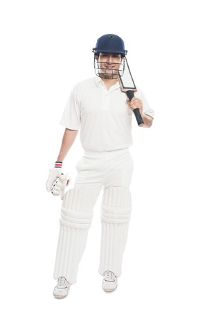 cricket bat: Portrait of a batsman standing with holding a cricket bat and smiling
