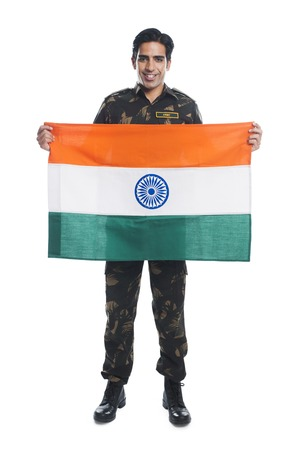 indian brave: Portrait of an army soldier holding Indian flag and smiling