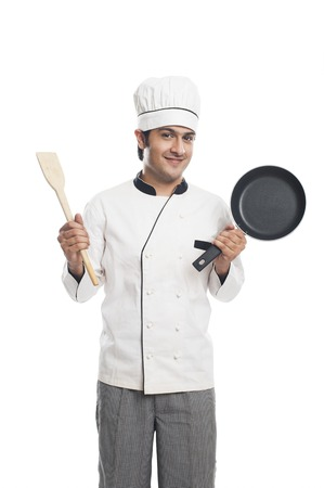 Portrait of a male chef holding a frying pan with spatula and smiling photo