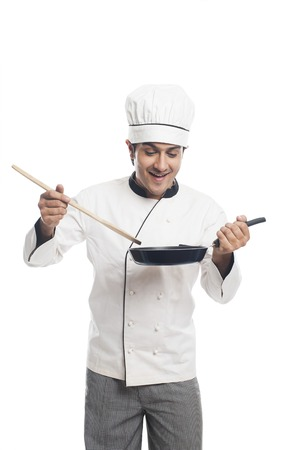 Male chef preparing food in a frying pan photo