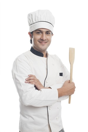 chefs whites: Portrait of a male chef holding a spatula and smiling