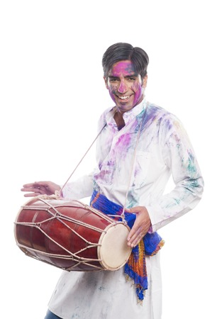 Man celebrating Holi with playing dholak photo