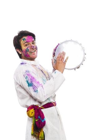 religious clothing: Man celebrating Holi with playing tambourine Stock Photo