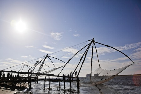 chinese fishing nets: Fishermen with Chinese fishing nets at a harbor, Cochin, Kerala, India Editorial