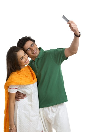 Couple taking a picture of themselves with a mobile phone photo