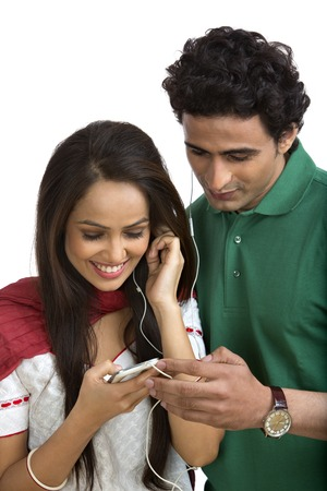 Couple listening to music on a mobile phone and smiling photo