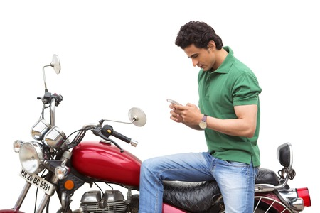 clipping  messaging: Man text messaging on a mobile phone while sitting on a motorcycle