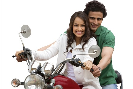 Portrait of a couple smiling while riding a motorcycle
