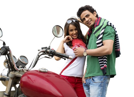 Couple standing beside a motorcycle and smiling photo