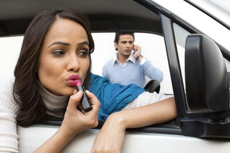 Woman applying lipstick in a car with her boyfriend talking on a mobile phone in background photo