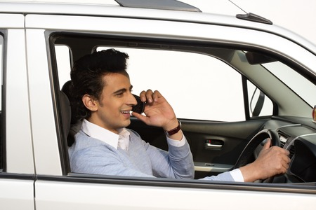 Man talking on a mobile phone while driving a car photo
