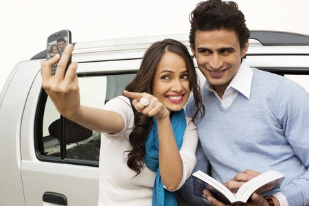 Couple taking picture of themselves with a mobile phone photo