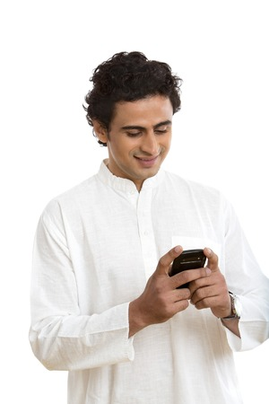 kurta: Man text messaging on a mobile phone and smiling