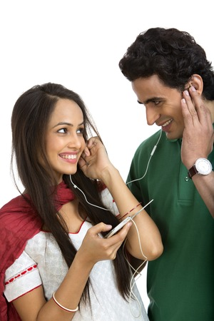 indian couple: Couple looking at each other while listening to music on a mobile phone