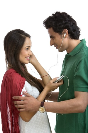 Couple looking at each other while listening to music on a mobile phone photo