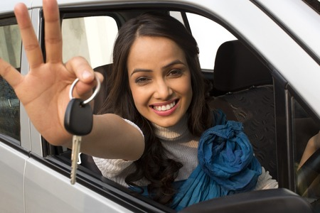 Portrait of a woman showing a car key while sitting in a car photo