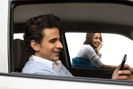 Man sitting in a car with his girlfriend talking on mobile phone in background photo