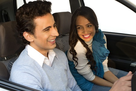 Couple sitting in a car and smiling photo