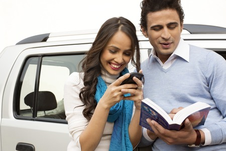 Woman text messaging with a mobile phone and man reading a book photo