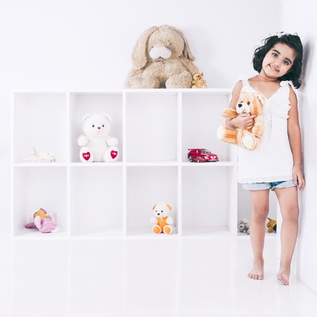 Portrait of a girl holding a teddy bear and smiling photo