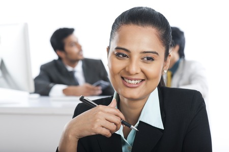 Businesswoman smiling in an office with their colleagues in the background photo