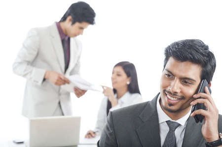 Close-up of a businessman talking on a mobile phone with his colleagues in the background Stock Photo