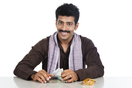 kurta: Portrait of a man counting money and smiling