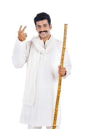 Portrait of a man holding a wooden staff and smiling