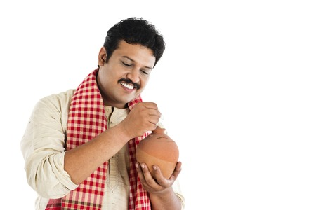 indian money: Man putting a coin into a piggy bank and smiling Stock Photo