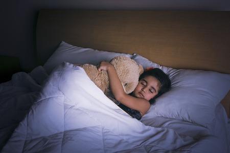 Girl sleeping on the bed with a teddy bear Stock Photo