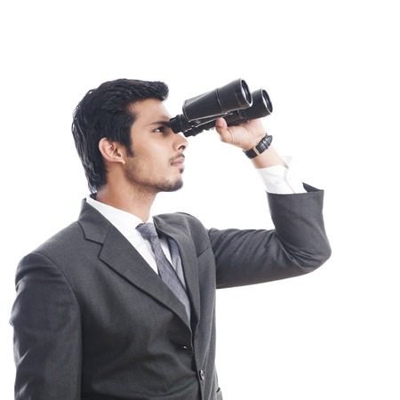 Businessman looking through binoculars photo