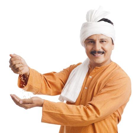 Portret van een boer die tarwe in zijn hand en glimlachend