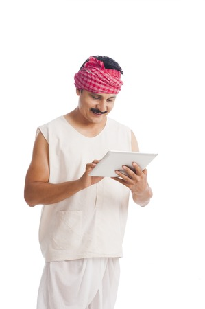 dhoti: Farmer using a digital tablet and smiling
