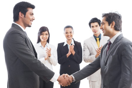 Two businessmen shaking hands with their colleagues applauding