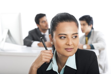 Close-up of a businesswoman holding a pen with her colleagues in the background photo