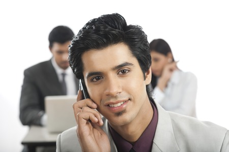 Portrait of a businessman talking on a mobile phone with his colleagues in the background