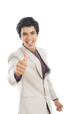 Portrait of a businessman showing thumbs up sign and smiling photo