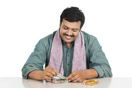 contando dinero: Sonriente hombre contar dinero Foto de archivo
