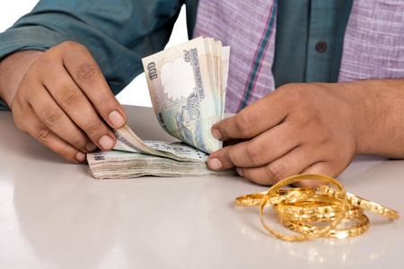 kurta: Mid section view of a man counting money