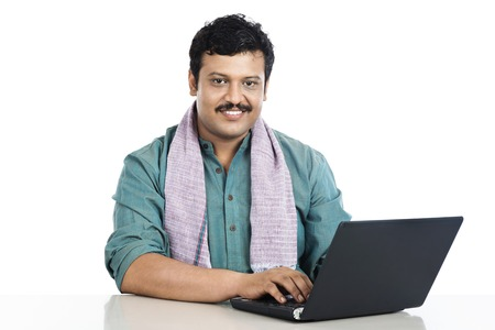 kurta: Portrait of a man using a laptop and smiling
