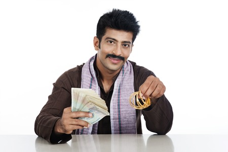 kurta: Portrait of a man holding money and golden bangles