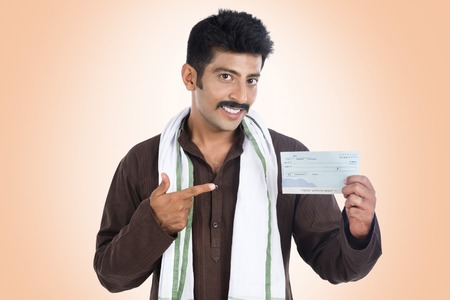 kurta: Portrait of a man pointing to a bank cheque and smiling