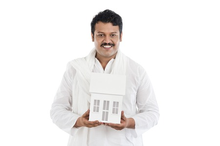 kurta: Portrait of a man holding a model home and smiling